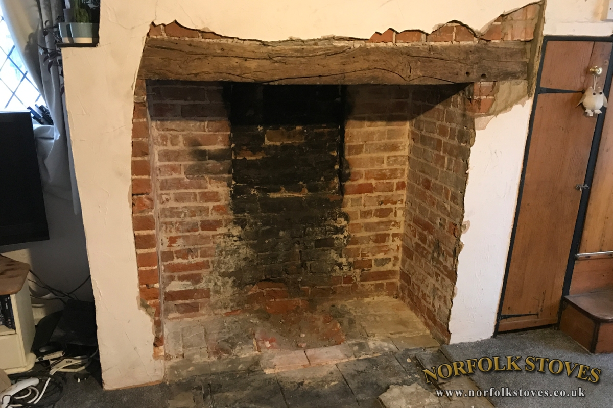 Large Fireplace opening with original beam an brickwork uncovered